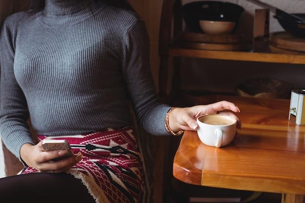 Metà di sezione della donna che per mezzo del telefono cellulare mentre bevendo una tazza di caffè