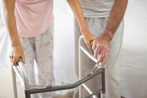 Metà di sezione della donna d'aiuto dell'uomo senior per camminare con il camminatore