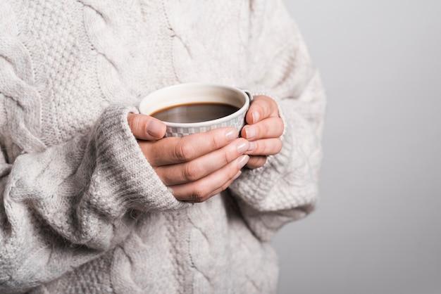 Metà di sezione della donna in vestiti di lana che tengono tazza di caffè