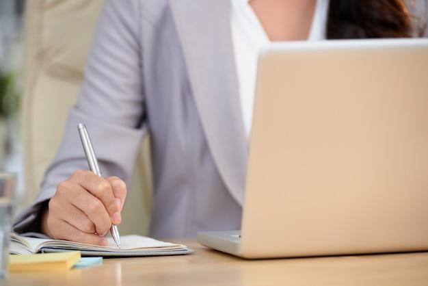 Metà di sezione della donna potata che copia i dati importanti dal computer portatile
