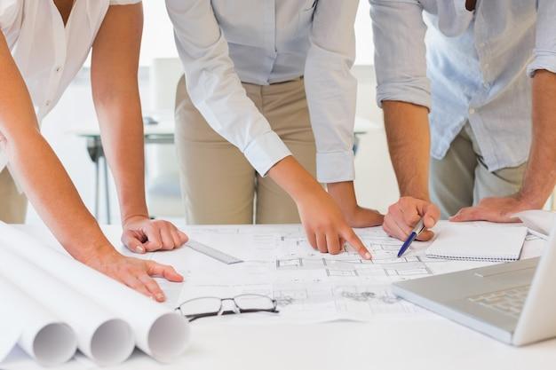 Metà di sezione della gente di affari che lavora ai modelli all'ufficio