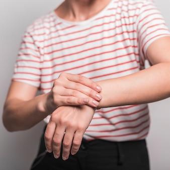 Metà di sezione della giovane donna che ha dolore in polso