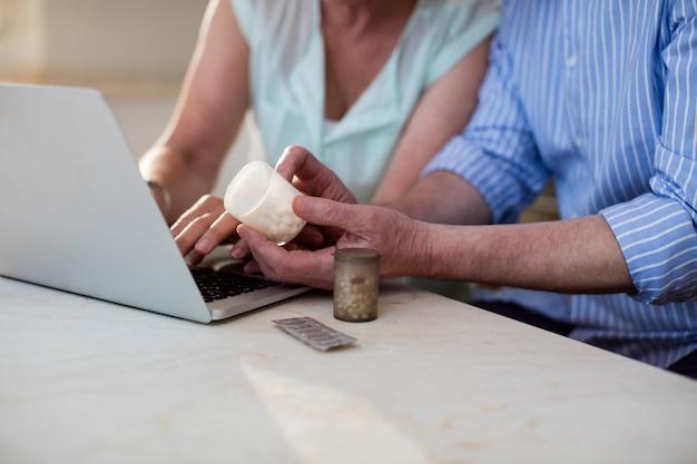 Metà di sezione delle coppie senior che controllano medicina sul computer portatile in cucina