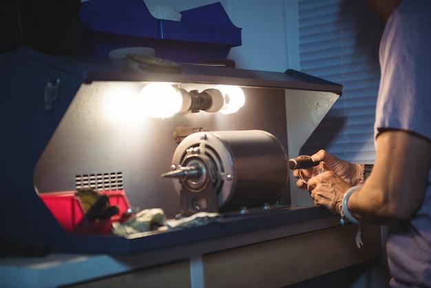 Metà di sezione di artigiana che lavora ad una macchina