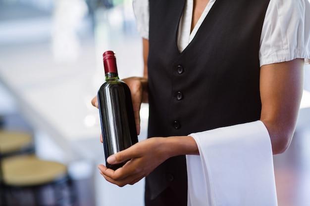 Metà di sezione di cameriera con una bottiglia di vino rosso e un asciugamano