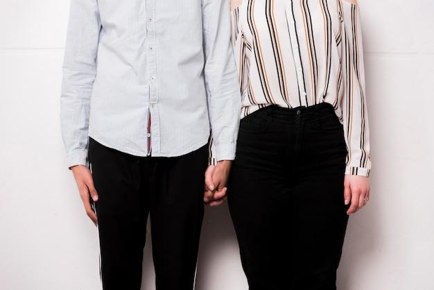 Metà di sezione di giovani coppie che tengono la mano di ciascuno che sta contro la parete bianca