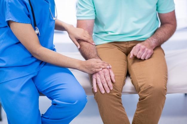 Metà di sezione di medico che consola paziente senior