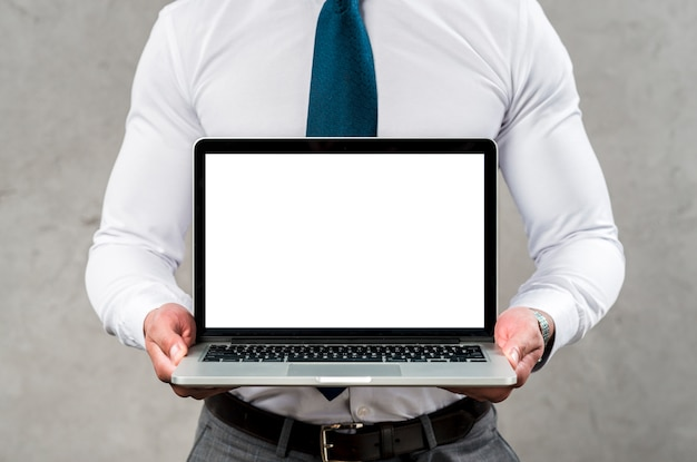 Metà di sezione di un computer portatile della tenuta dell'uomo con lo schermo bianco in bianco contro la parete grigia