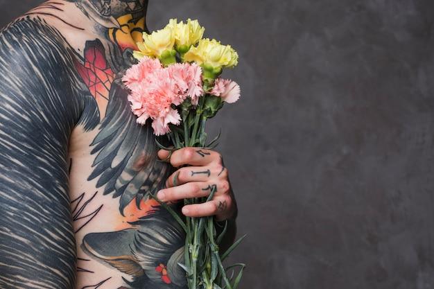 Metà di sezione di un giovane tatuato senza camicia che tiene garofano in mani