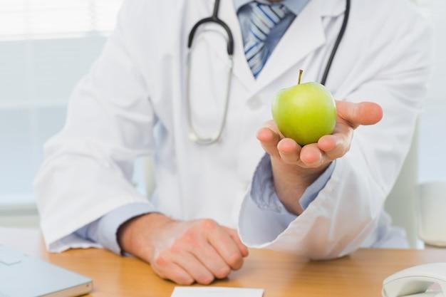 Metà di sezione di un medico maschio che tiene una mela