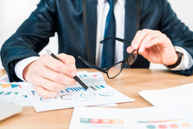 Metà di sezione di un uomo d'affari che giudica gli occhiali neri a disposizione che analizzano il grafico sulla tavola di legno
