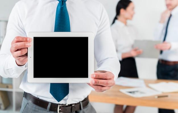 Metà di sezione di un uomo d'affari che mostra compressa digitale dello schermo in bianco nel luogo di lavoro