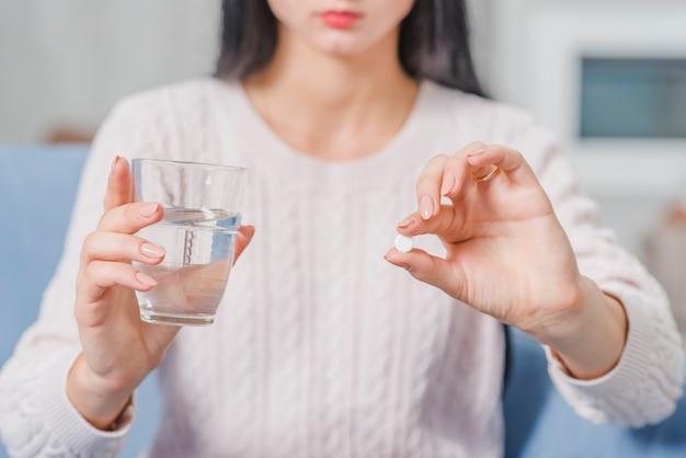 Metà di sezione di una donna che tiene compressa bianca e bicchiere d'acqua in mani