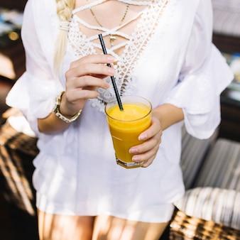 Metà di sezione di una donna che tiene il succo di mango in vetro
