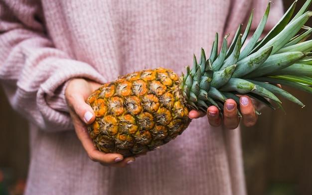 Metà di sezione di una persona che tiene intero ananas