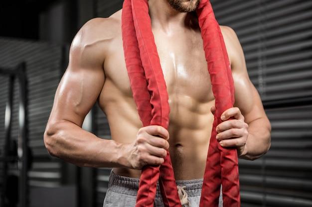 Metà di sezione di uomo a torso nudo con corda di battaglia intorno al collo presso la palestra di crossfit