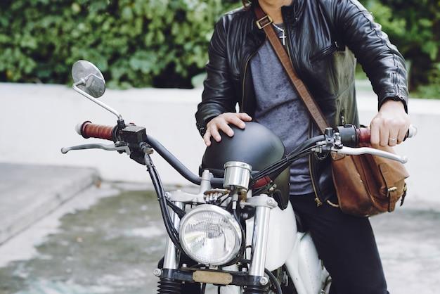 Metà di sezione di uomo irriconoscibile in giacca di pelle con casco seduto su una moto