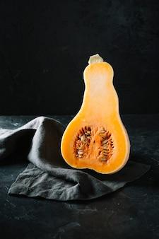 Metà di zucca butternut organica cruda su fondo e panno neri