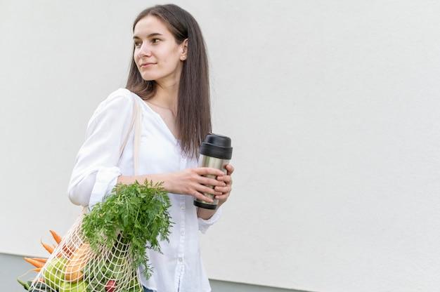 Metà donna del colpo che tiene borsa riutilizzabile con generi alimentari e thermos fuori