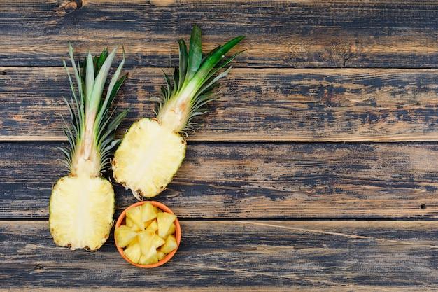Metà e fette dell'ananas in una ciotola arancio sulla vecchia superficie di legno di lerciume, vista superiore.