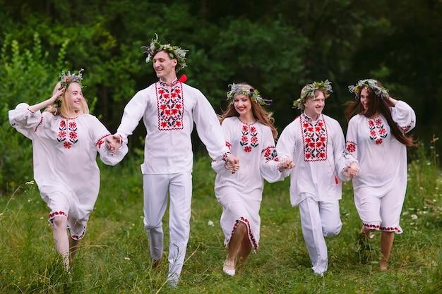 Metà estate, persone che corrono nella natura in abiti slavi.
