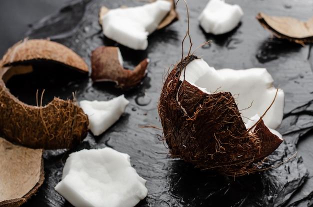 Metà fresca della noce di cocco cruda riempita di pezzi. bellezza e benessere