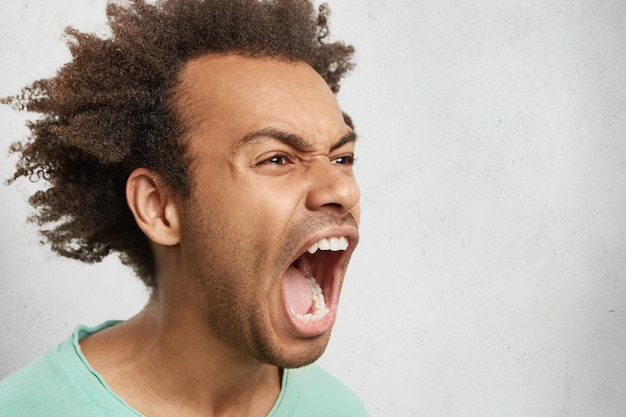 Metà profilo di maschio aggressivo con capelli ricci scuri, apre ampiamente la bocca, urla in preda al panico