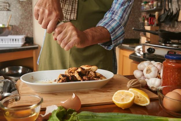 Metà sezione og cuoco anonimo condimento con pepe