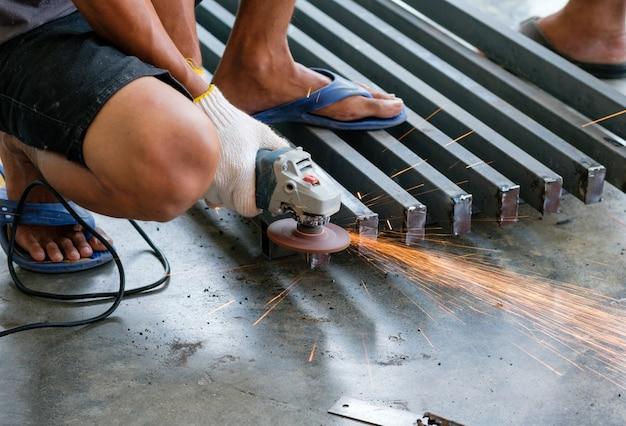 Metallo di taglio operaio con smerigliatrice con scintille