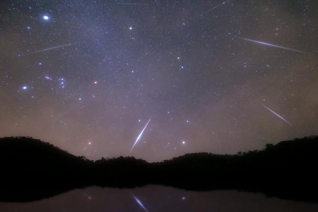Meteora geminid nel cielo notturno nel lago