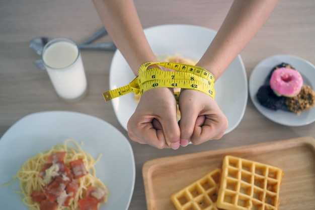Metro a nastro intorno alle braccia delle donne. smetti di mangiare grassi trans, spaghetti, ciambelle, waffle e dolci. perdere peso per una buona salute. concetto di dieta vista dall'alto