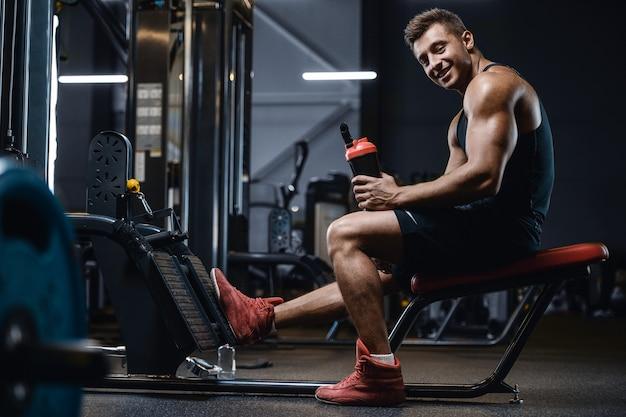 Metta in mostra l'acqua potabile dell'uomo muscolare di forma fisica dopo l'allenamento