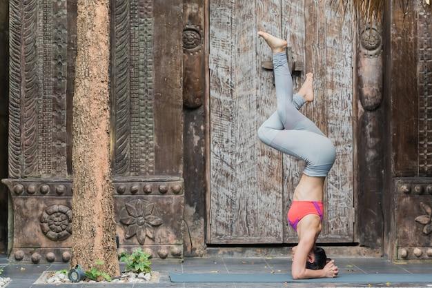Metta in mostra l'allenamento della giovane donna con la posa di yoga a casa.
