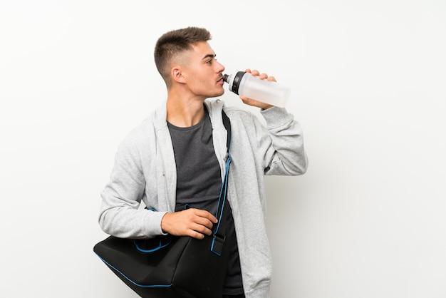 Metta in mostra l'uomo sopra la parete bianca isolata con una bottiglia di acqua