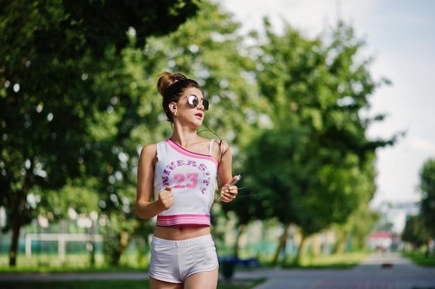 Metta in mostra l'usura della ragazza sugli shorts bianchi di american national standard della camicia che funzionano al parco.
