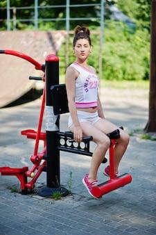 Metta in mostra l'usura della ragazza sulla camicia bianca di american national standard degli shorts che fa gli esercizi sui simulatori all'aperto al parco.