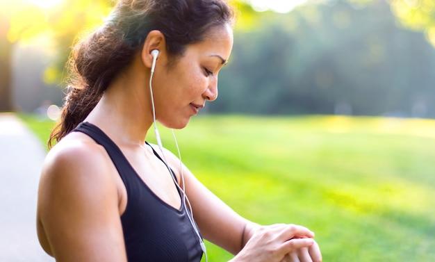 Metta in mostra la donna asiatica che ascolta la musica con le cuffie mentre esamina l'orologio all'aperto