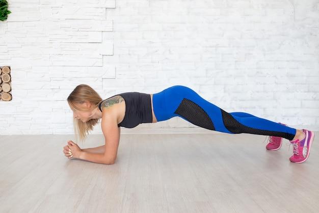 Metta in mostra la donna che fa la plancia per rafforzare i suoi bicipiti tricipiti e addominali. concetto di sport femminile.
