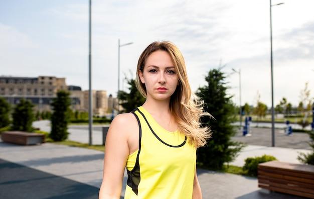 Metta in mostra la donna in attrezzature gialle in un parco.