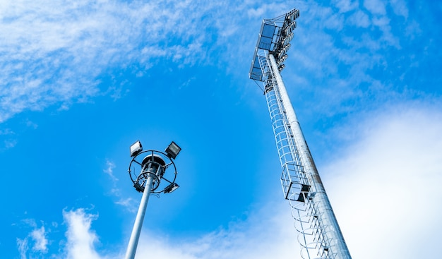 Metta in mostra le luci dello stadio su bello cielo blu e sulle nuvole bianche. copia spazio