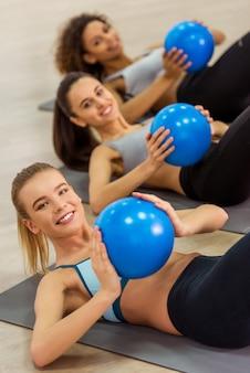 Metta in mostra le ragazze che sorridono mentre risolvono con la palla di forma fisica.