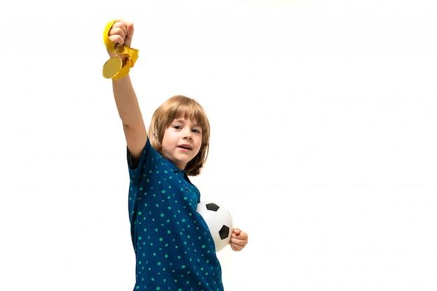 Mette in mostra il ragazzo del vincitore che tiene un pallone da calcio e una medaglia in sue mani su un bianco