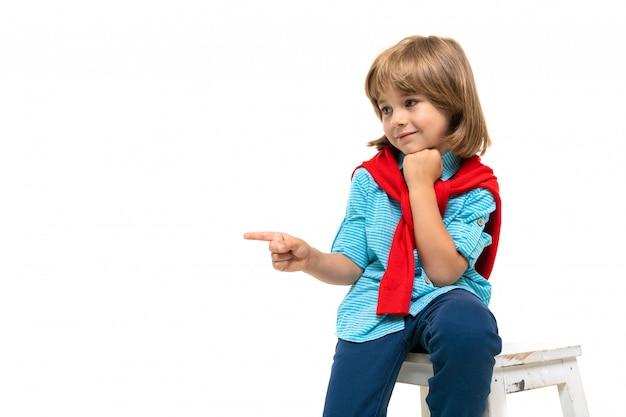 Mette in mostra il ragazzo dell'adolescente in maglietta con la maglia con cappuccio intorno al collo che gesticola sulla parete bianca