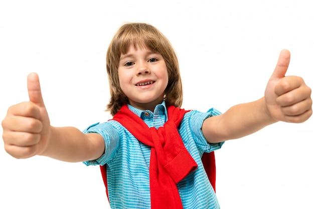 Mette in mostra il ragazzo dell'adolescente in maglietta con la maglia con cappuccio intorno al collo che gesticola sulla parete blu