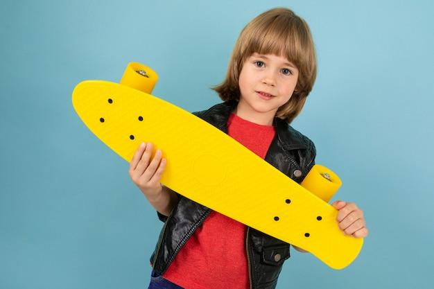 Mette in mostra il ragazzo dell'adolescente in maglietta rossa e giacca nera con il penny giallo sulla parete blu