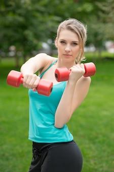 Mette in mostra l'esercizio della ragazza con le teste di legno nel parco