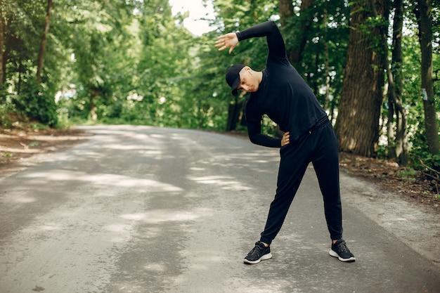 Mette in mostra l'uomo in un parco dell'estate di mattina