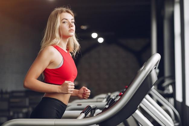 Mette in mostra la donna bionda in un addestramento degli abiti sportivi in una palestra