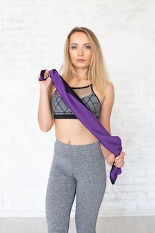 Mette in mostra la donna con l'asciugamano viola. concetto di fitness