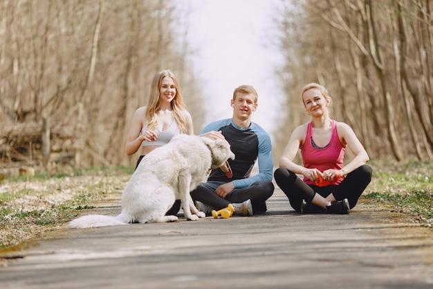 Mette in mostra la famiglia che si siede in una foresta dell'estate